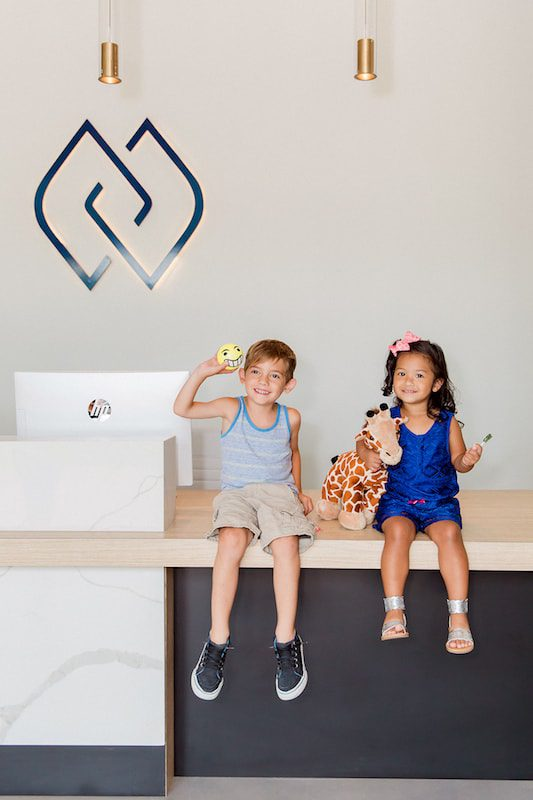 young patients sitting on the front desk with treats and toys