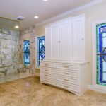 Berardo Bathroom Renovation with white cabinets, stained glass, tiled floor, and walk in shower