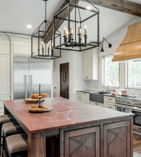 Cross Kitchen Remodel with double chandelier, red counter top on island, and copper vent hood