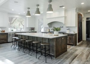 Bates Kitchen Renovation with large kitchen island, bar stools, white cabinets, and wood floors