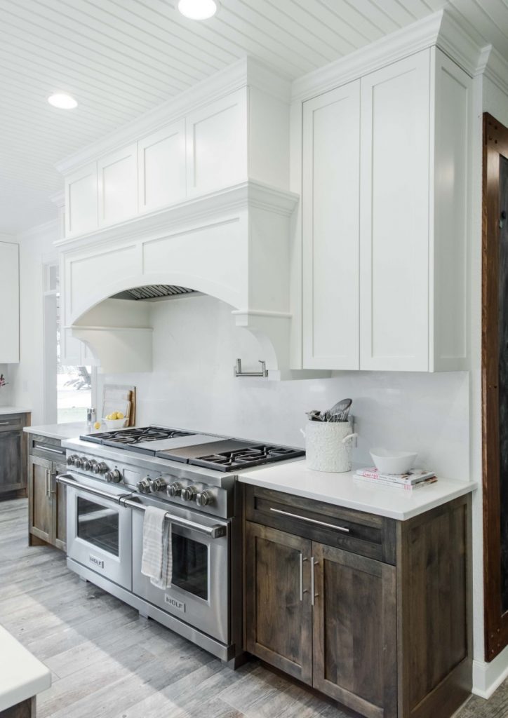 Bates Kitchen Renovation with white vent hood, stainless steel appliances, white marble counter top, and brown cabinets