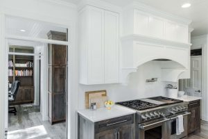 Bates Kitchen Renovation with white vent hood, stainless steel appliances, white marble counter top, and view of home office