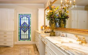 Berardo Bathroom Renovation with white cabinets, stained glass, tiled floor, and marble double vanity
