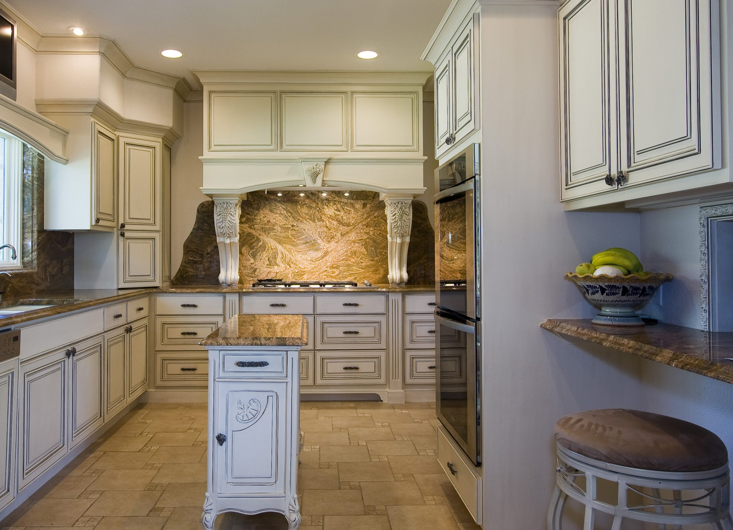 Clack kitchen renovation with marble backsplash, white cabinets, and custom vent hood, with double oven, and desk area