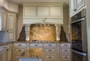 Clack kitchen renovation with marble backsplash, white cabinets, and custom vent hood, with double oven
