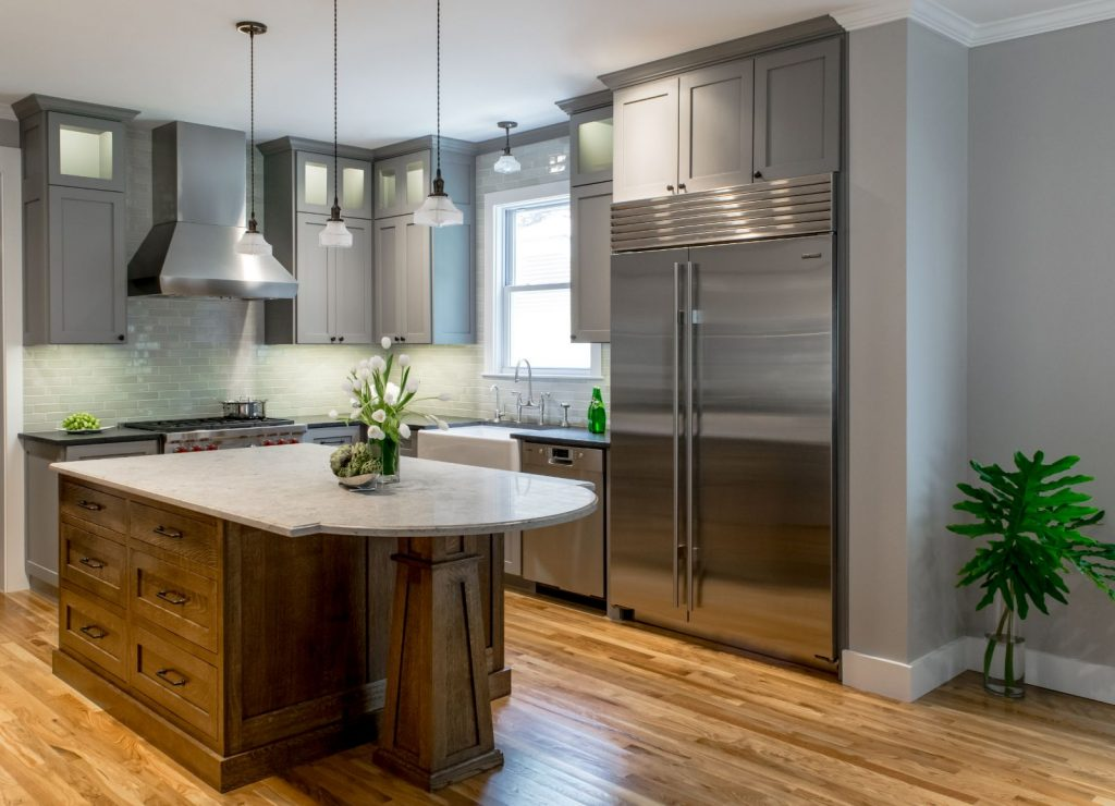 Donnelly Kitchen side view, with wood floors, stainless steel appliances, light grey cabinets, and kitchen island