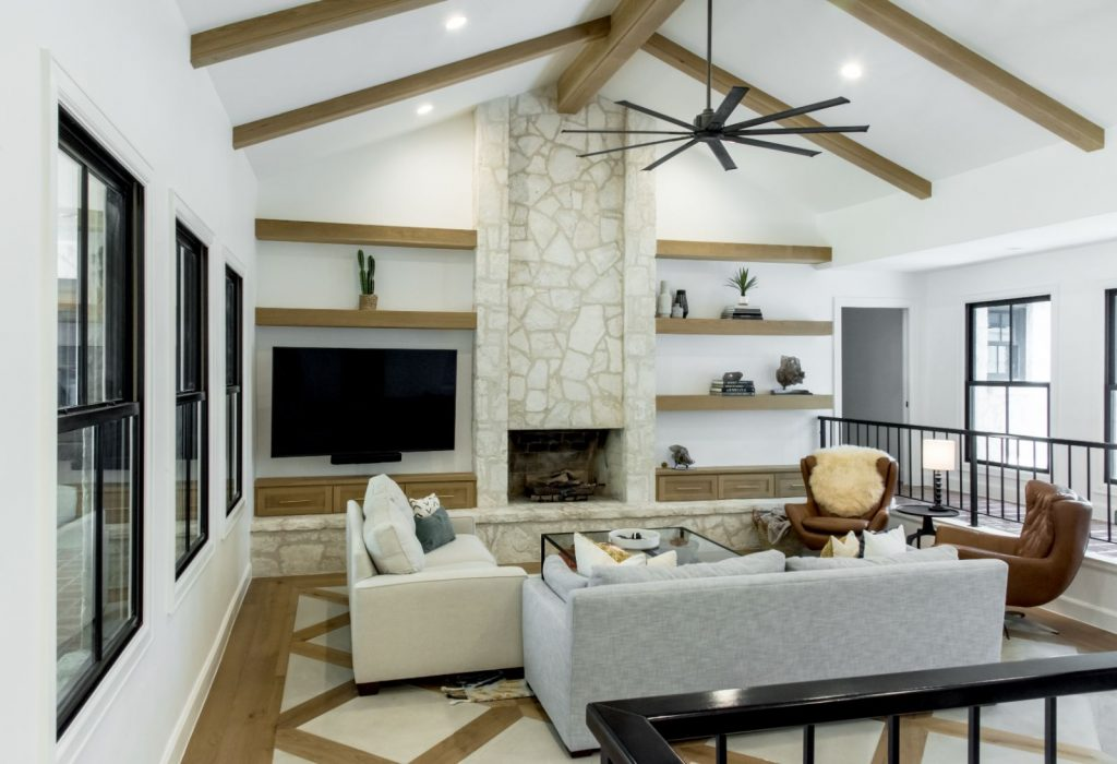 Edwards Marshall Special Project Living room with wood beams, black rails, and stone fire place