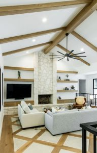 Edwards Marshall Special Project Living room with wooden beems, pattern floor, and stone fireplace