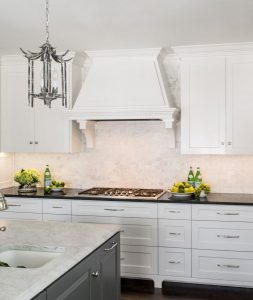 Hagee Kitchen Renovation with white cabinets, black and marble counter tops, and hanging light fixtures