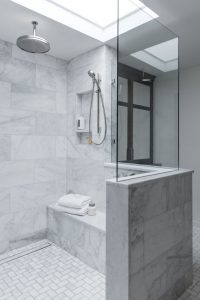 Hall bathroom Renovation with walk in shower, water fall shower head, and marble tiled wall