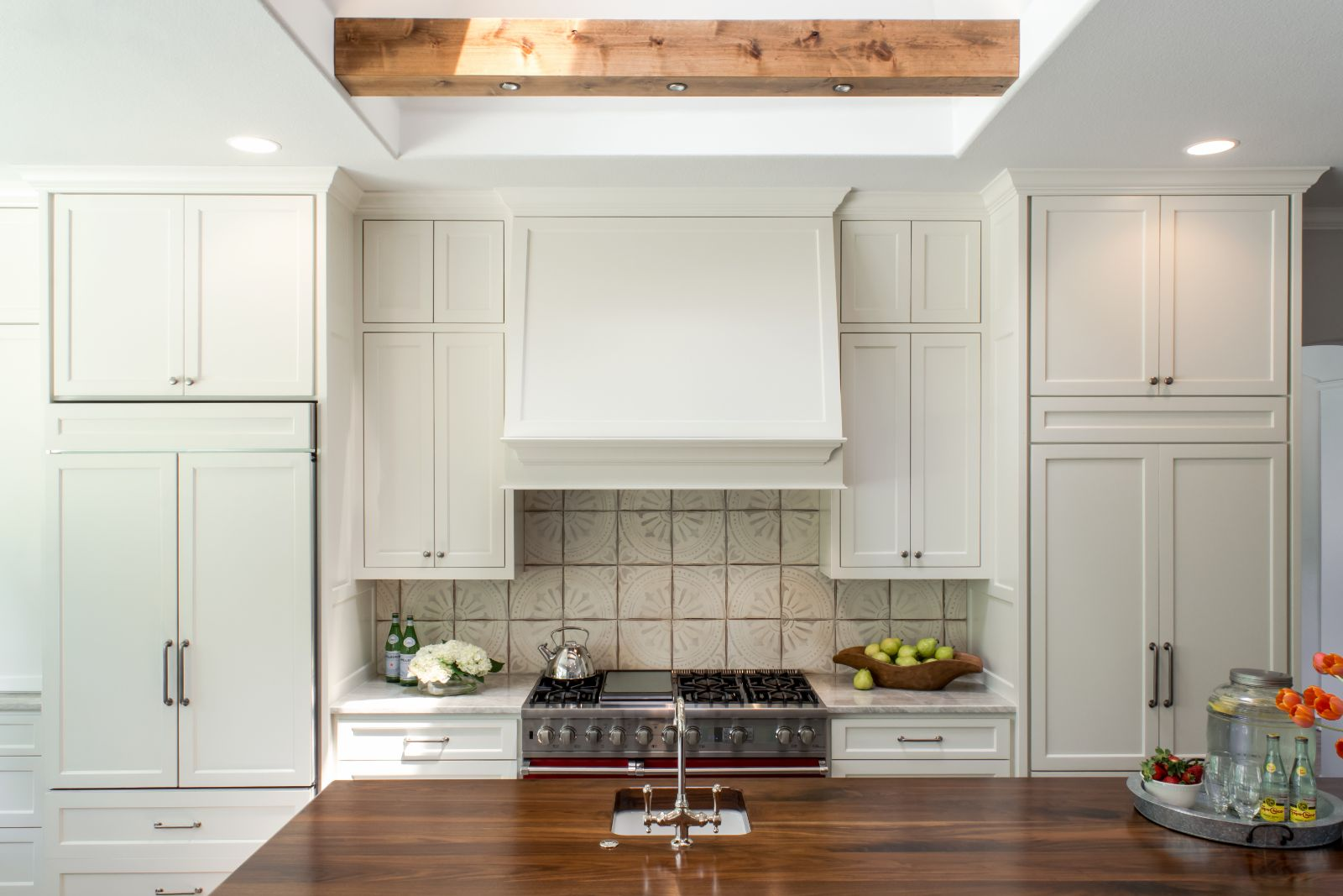 Hirko Kitchen Renovation with white cabinets from floor to ceiling, wooden kitchen island, and tile back splash