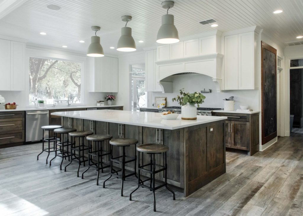 Kitchen remodel with wood floors, white plaster, white counter tops, and large kitchen island