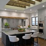 Mezey Kitchen Renovation with butterfly stone back splash over stove top, light green cabinets, decorative wooden beam and kitchen windows, double oven, kitchen island and stone walls