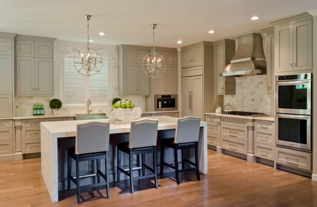 Penner Kitchen Renovation with marble counter top, large kitchen island , green cabinets, and double oven