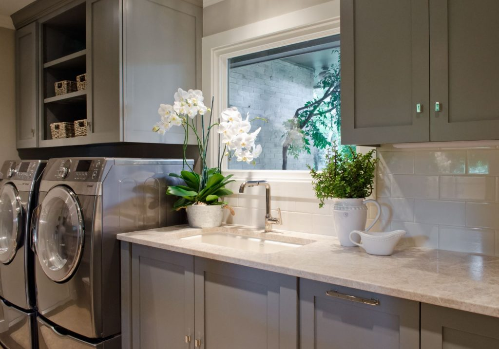 Penner Laundry room renovation with grey cabinets, counter with sink, and window