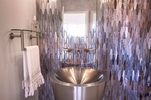 Rath Bathroom Renovation with tiled purple metallic wall, stainless steel sink, and oval mirror