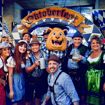 People in costume in front of Oktoberfest banner