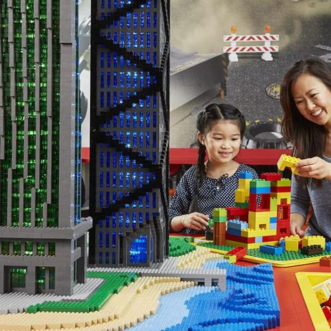 Child and mom building near LEGO model of a city