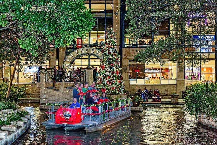 Carolers on a river boat in front of Rivercenter's Christmas tree