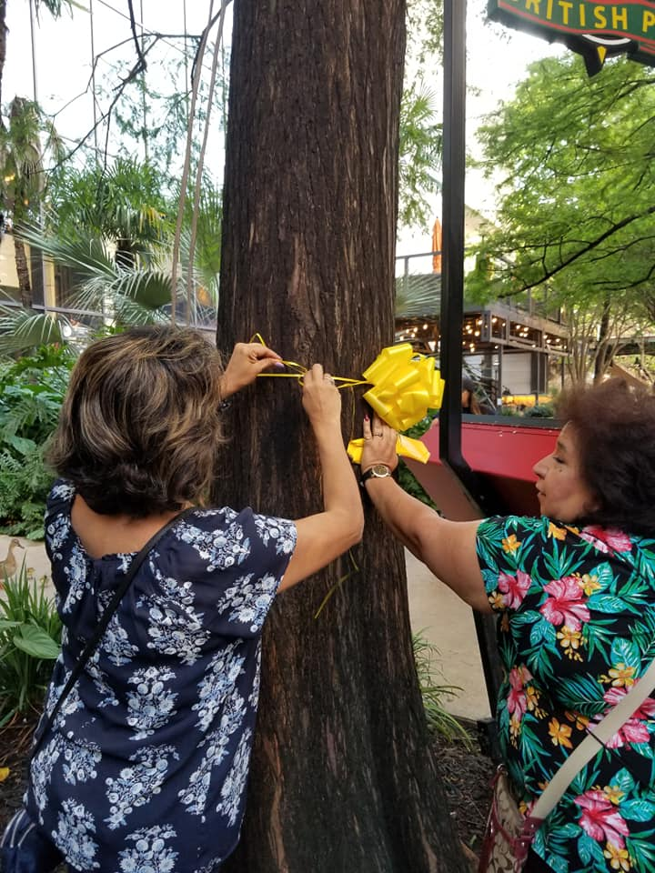 Volunteers tying a ribbon around a tree