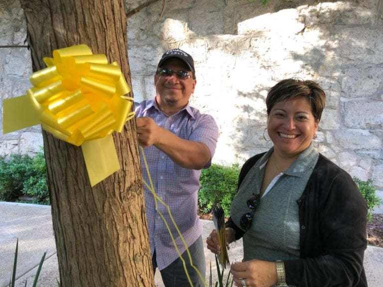 Volunteers tying a yellow ribbon around a tree