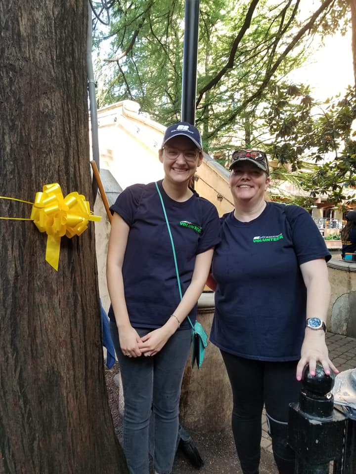 Volunteers standing near a yellow ribbon
